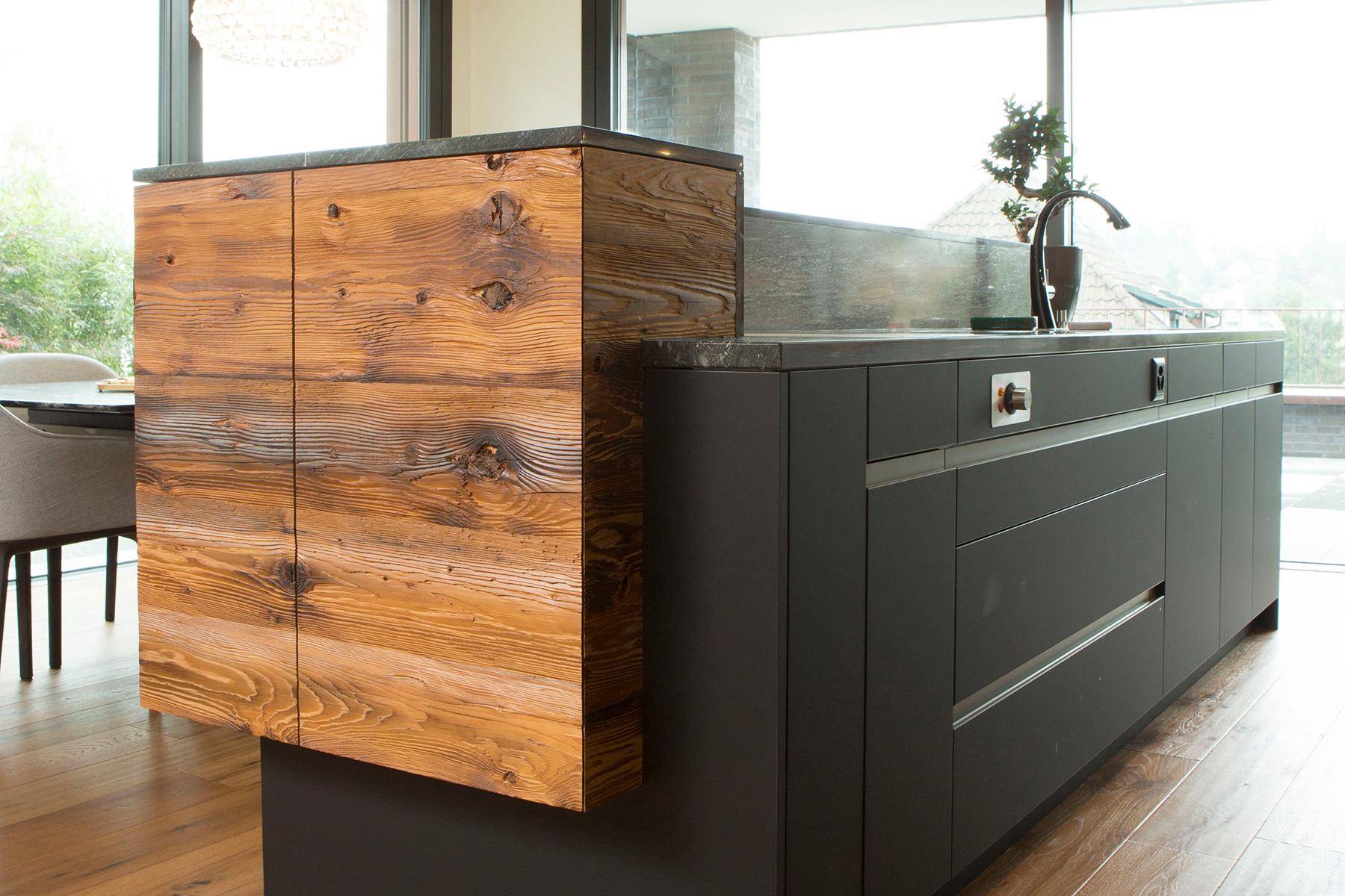 Kücheninsel in Valser Quarzit poliert. Küche mit schwarzen Armaturen.